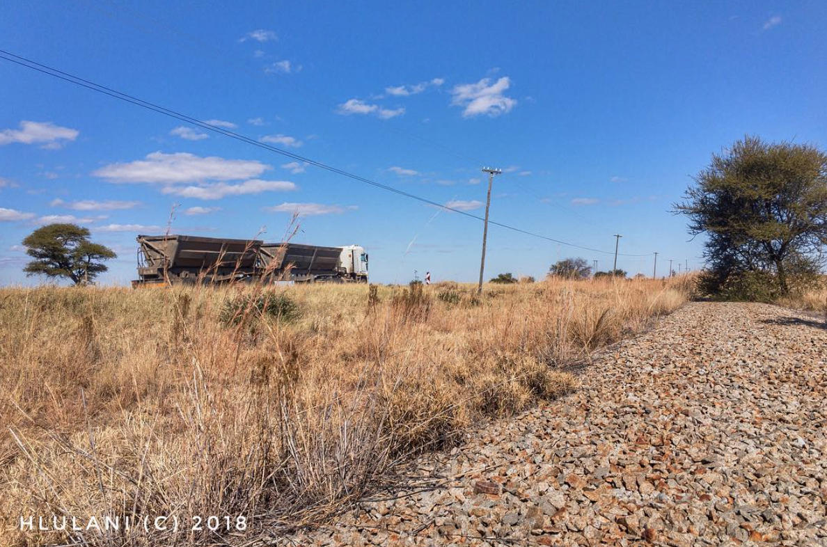 The photo shows a road freight truck along the vanishing point, with a stolen railway line on the lower end of the vanishing point. Between the two, there is a bush, trees and powerlines against the backdrop of bright blue Limpopo skies.
